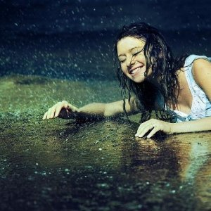 A girl is laying in the rain smiling broadly with joy