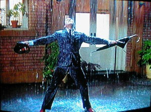 A man stands happily in the rain (from Singing in the Rain)