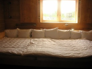 Large and inviting bed with white pillows and linens in the sun