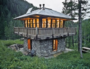 tiny home in a clearing made of stone and wood