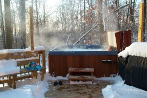 A woman reclines in a bubbling hot tub on a snowy deck