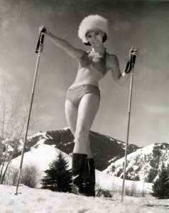A pin up girl poses with her ski poles and boots and a jaunty fuzzy hat