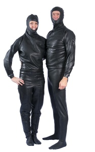 A couple pose side by side is black rubber suits with only their faces uncovered